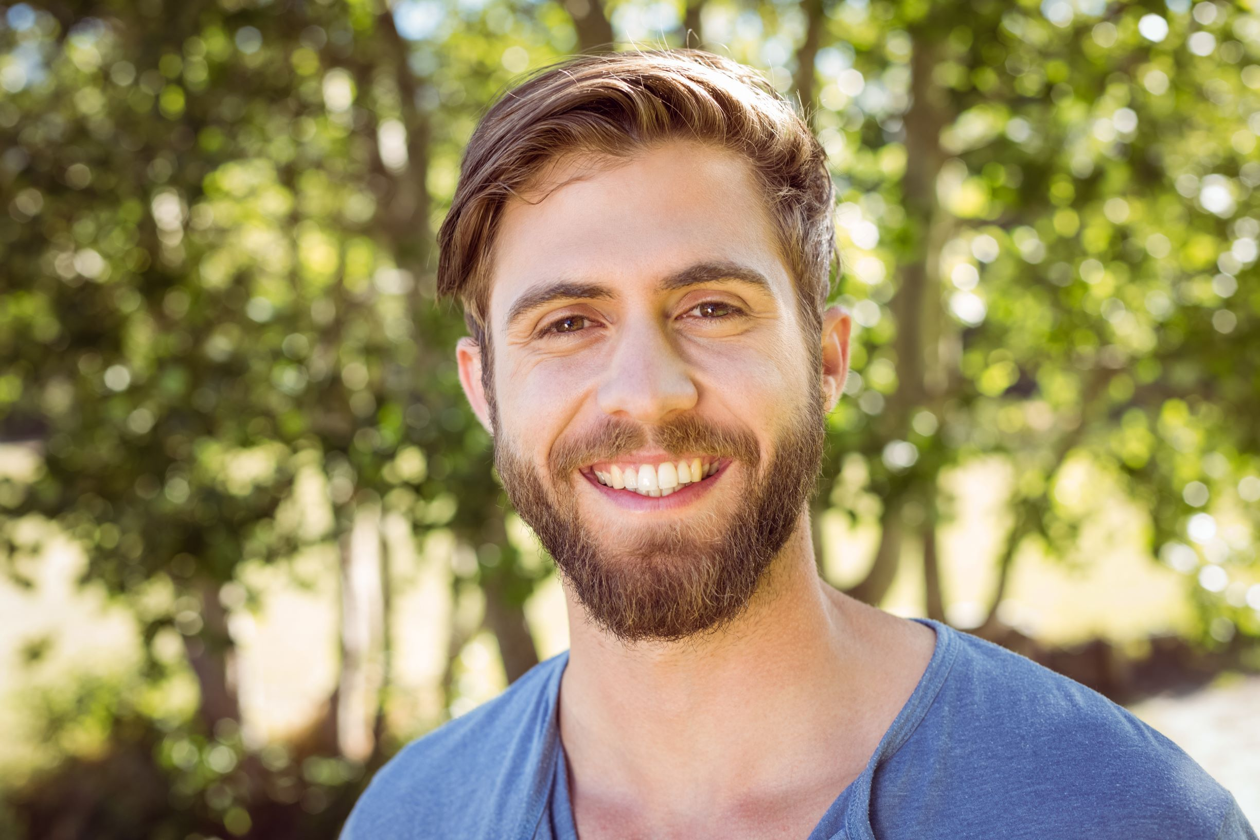 Photo: Young man with beard, smiling at camera
